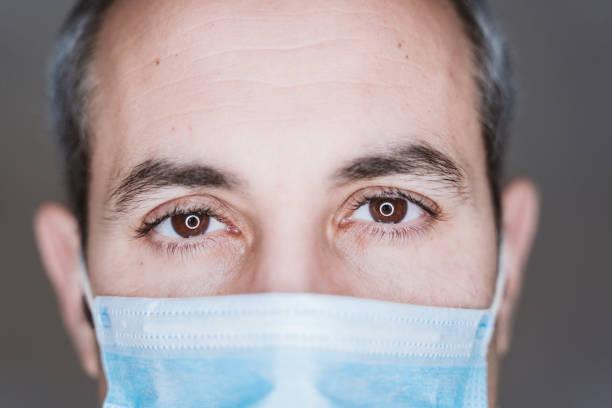 vista de cerca del hombre médico usando máscara protectora y estetoscopio. Concepto Coronavirus Covid-19 - foto de stock