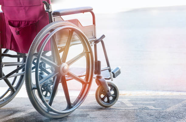 close up view of empty wheelchair with pavement handicap symbol - wheelchair stock photos and pictures
