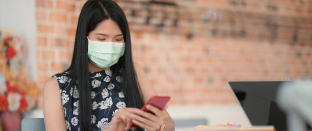 Close up view of female college student wearing mask using smartphone to relax from doing homework