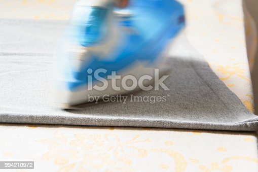 868537890 istock photo Close up view of female hand ironing a t-shirt with steam iron, housework concept 994210972