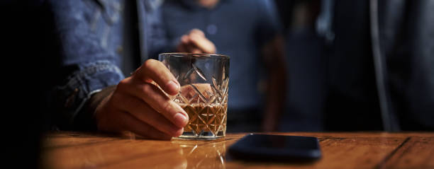 Close up view of glass with alcohold. Man's hand holds it. Smartphone on the table. Horizontal photo stock photo