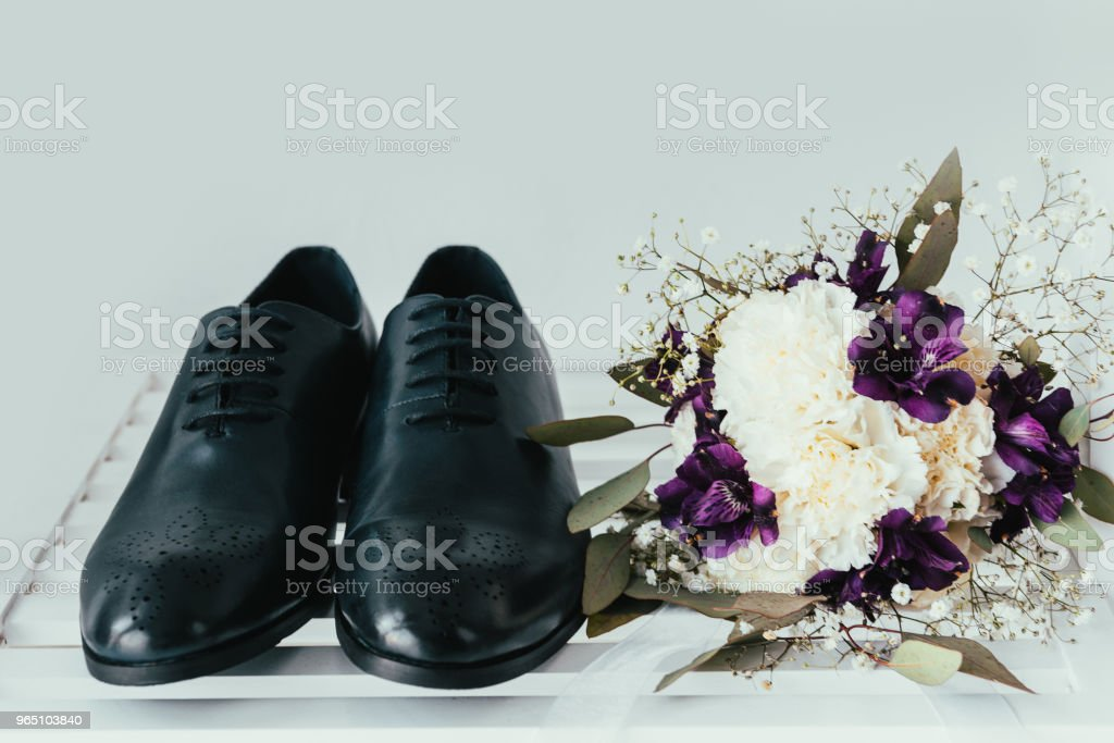 close up view of grooms shoes and bridal bouquet on grey background royalty-free stock photo