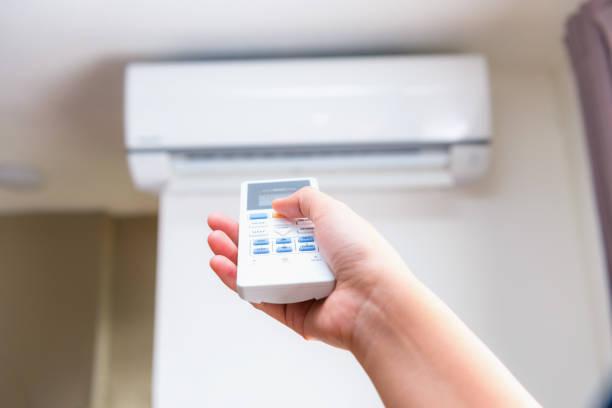 エアコンのリモコンを操作する手のクローズ アップ表示 - エアコン ストックフォトと画像