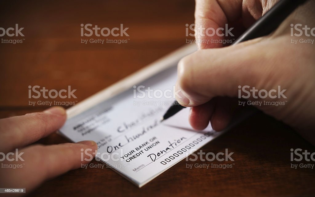 Close up View of Hand Writing A Donation Check Writing a donation check to a charitable organization Charitable Donation Stock Photo