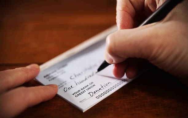 Close up View of Hand Writing A Donation Check stock photo