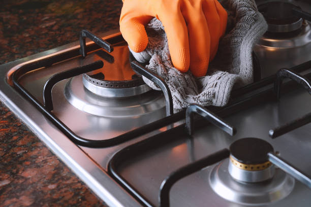 Close up view of hands in rubber gloves cleaning hob stock photo