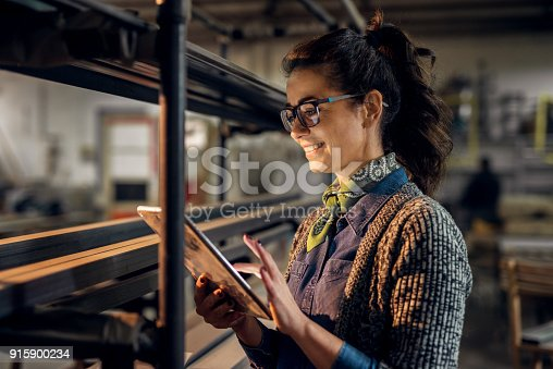 istock Close up view of hardworking focused professional motivated business woman holding a tablet next to the shelf with metal pipes in the fabric workshop. 915900234