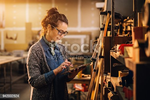 915900234istockphoto Close up view of hardworking focused professional motivated business woman holding a tablet next to the shelf with tools in the fabric workshop. 942002524