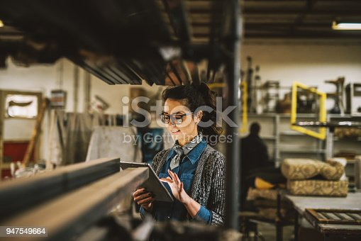 915900234istockphoto Close up view of hardworking focused professional motivated business woman holding a tablet next to the shelf with metal pipes in the fabric workshop. 947549664