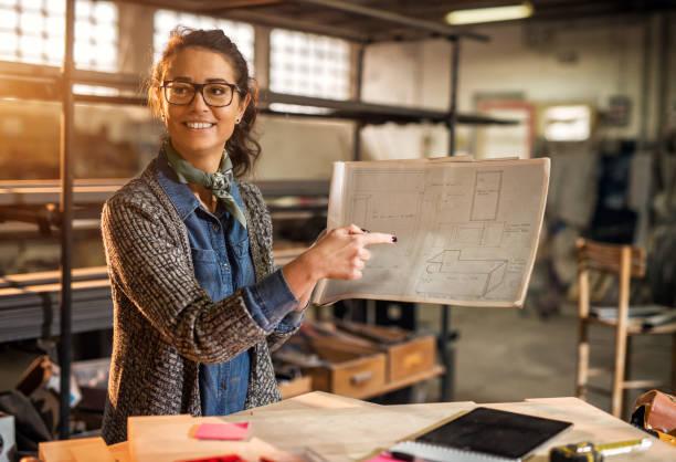 cerrar vista de trabajador feliz había centrado a mujer ingeniero profesional motivado señalando en un proyecto de planos en el taller de tela soleado. - arquitecta fotografías e imágenes de stock