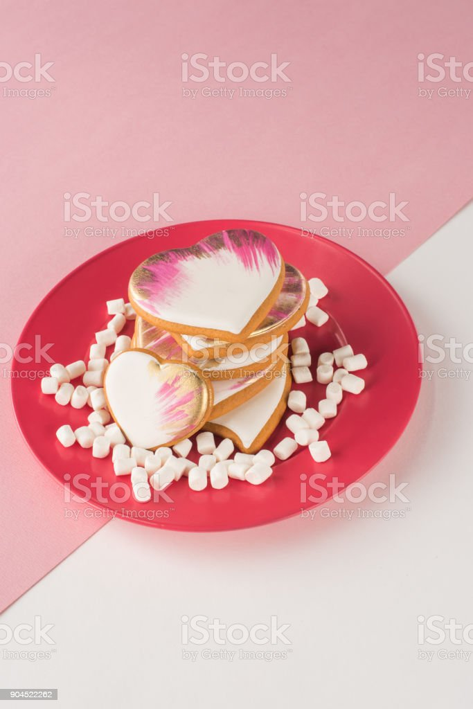 close up view of heart shaped cookies and marshmallow on pink plate stock photo