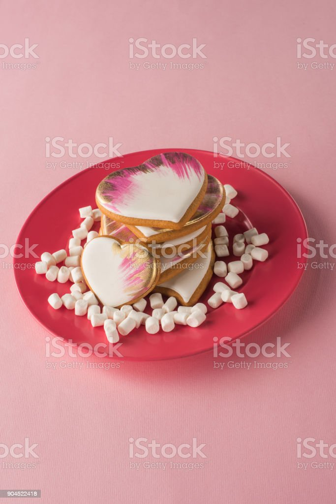 close up view of heart shaped cookies and marshmallow on plate isolated on pink stock photo