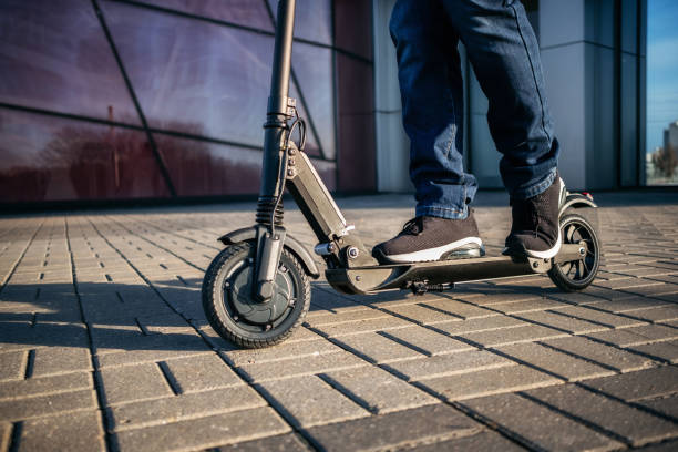 Close up view of legs of man on electric scooter stock photo