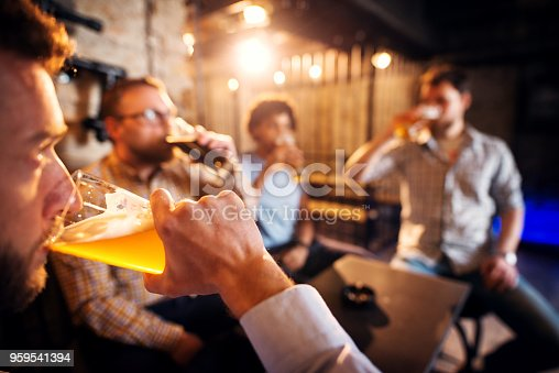 istock Close up view of man drinking beer while sitting in the pub with friends. 959541394