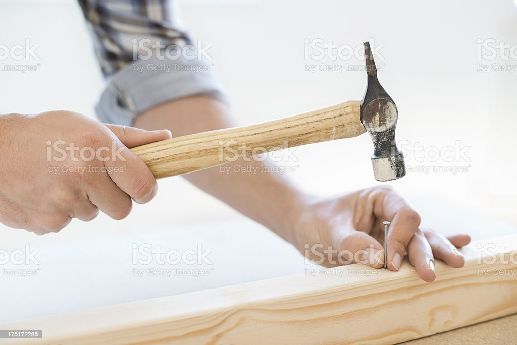Close up view of man hammering nail into wooden plank stock photo