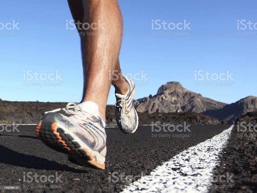 Close up view of man running on asphalt in running shoes stock photo