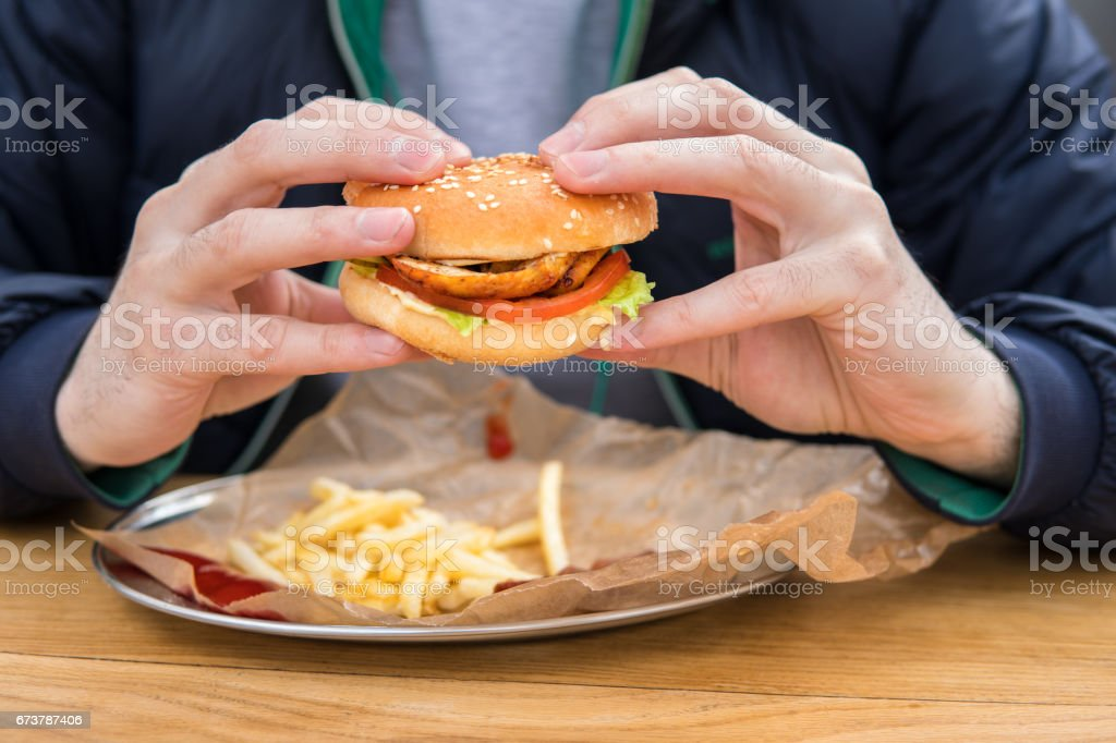adamın elleri ile Amerikan burger görünümünü kapatın. royalty-free stock photo