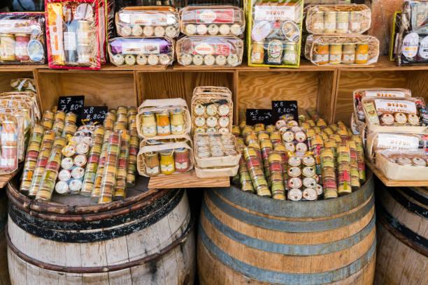 Eine Nahaufnahme von vielen verschiedenen Arten von Dijon Senf in Regalen und alten Weinfässern – Foto
