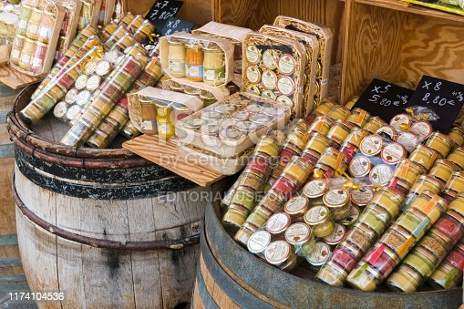Dijon, Burgundy / France - 27 August 2019: view of many different types of Dijon mustard on shelves and old wine casks