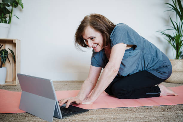 close up view of mature caucasian senior woman practicing yoga pose at home. using laptop for online class with teacher. Healthy and technology lifestyle stock photo