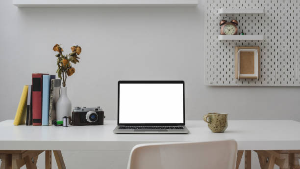 Close up view of office room with blank screen laptop, office supplies, camera, coffee cup and decorations on withe wooden