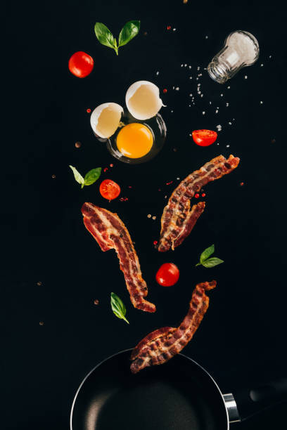 close up view of pieces of bacon, cherry tomatoes and raw egg yolk falling on frying pan isolated on black - food styling stock photos and pictures