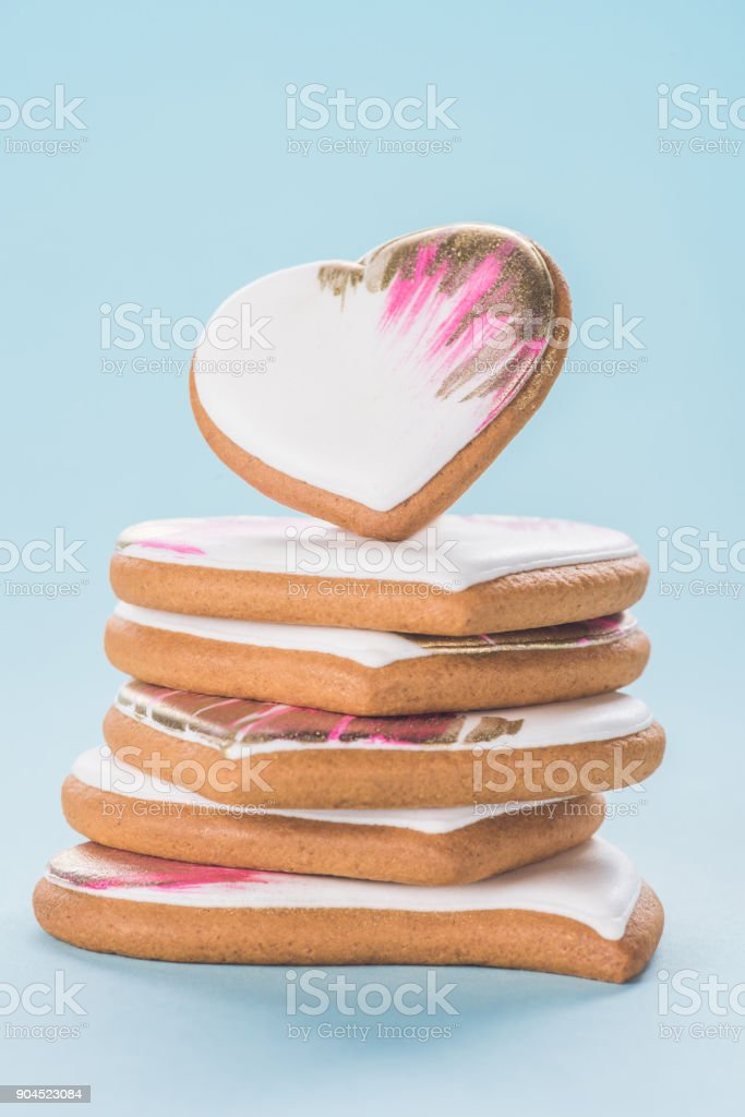 close up view of pile of glazed heart shaped cookies isolated on blue, st valentines day concept stock photo