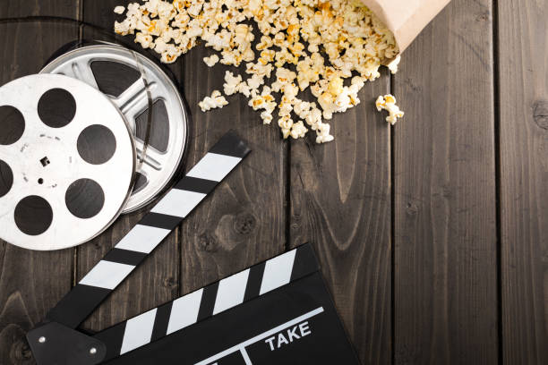 close up view of popcorn in paper container and movie clapper board on table, movie time concept - biglietto del cinema foto e immagini stock