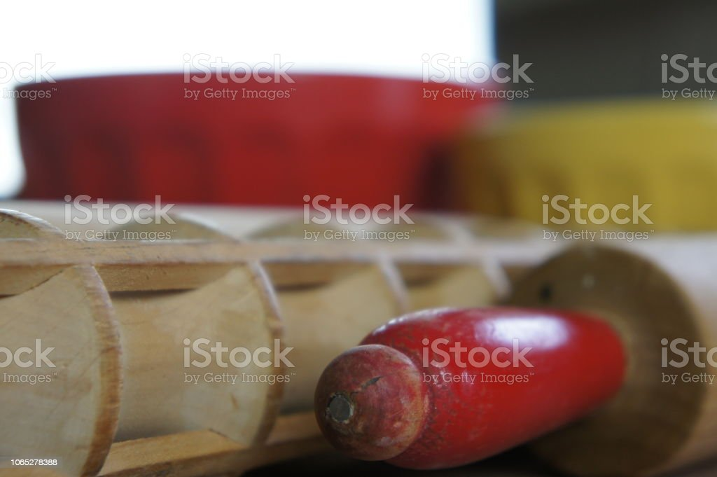 Close up view of rolling pins on a counter with bowls in the background stock photo