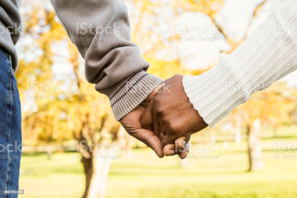 Close up view of senior couple holding hands stock photo