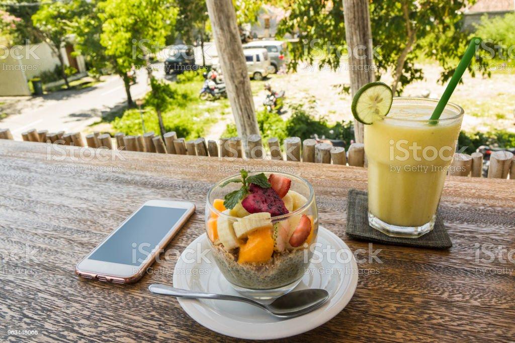 z bliska na smartfon, koktajl i danie ze świeżymi owocami na drewnianym blacie - Zbiór zdjęć royalty-free (Bali)