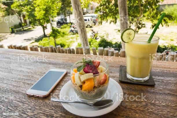 Z Bliska Na Smartfon Koktajl I Danie Ze Świeżymi Owocami Na Drewnianym Blacie - zdjęcia stockowe i więcej obrazów Bali