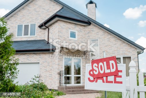 close up view of sold sign on wooden placard with sale sign in front of modern cottage