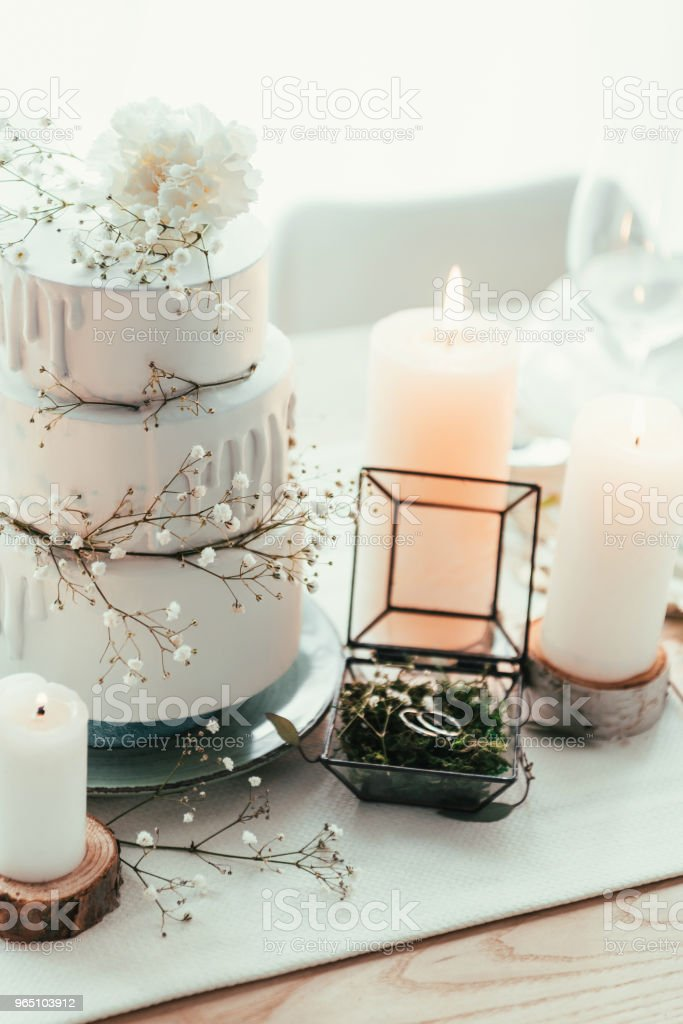 close up view of stylish table setting with candles and wedding rings for rustic wedding royalty-free stock photo