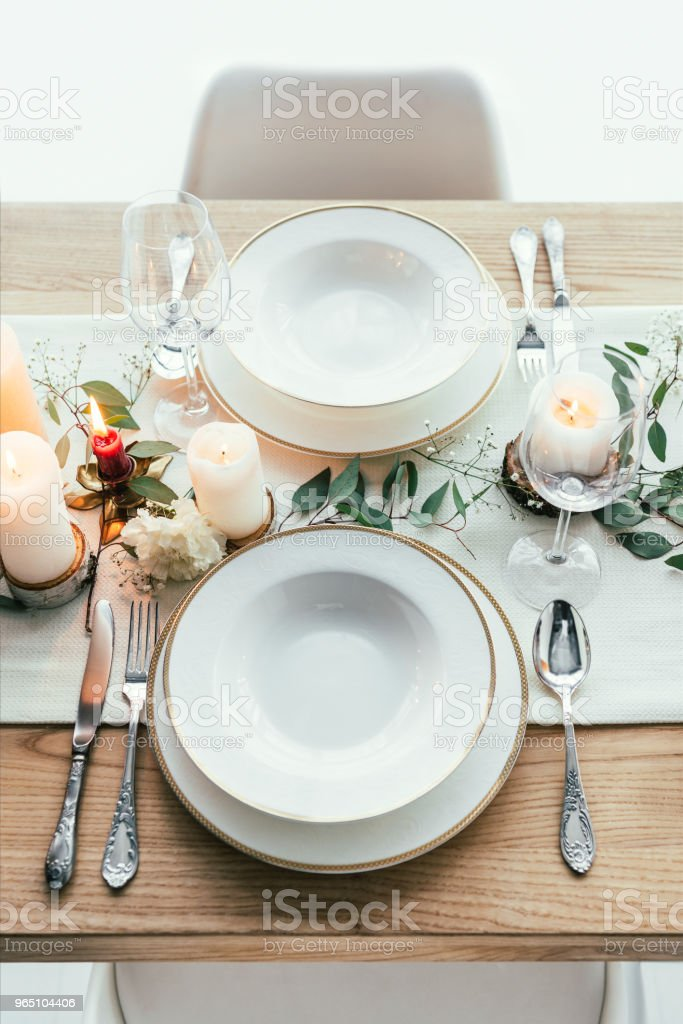 close up view of stylish table setting with candles, empty wineglasses and plates for rustic wedding zbiór zdjęć royalty-free