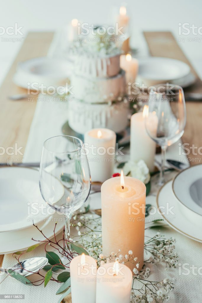 close up view of stylish table setting with candles, empty wineglasses and plates for rustic wedding royalty-free stock photo