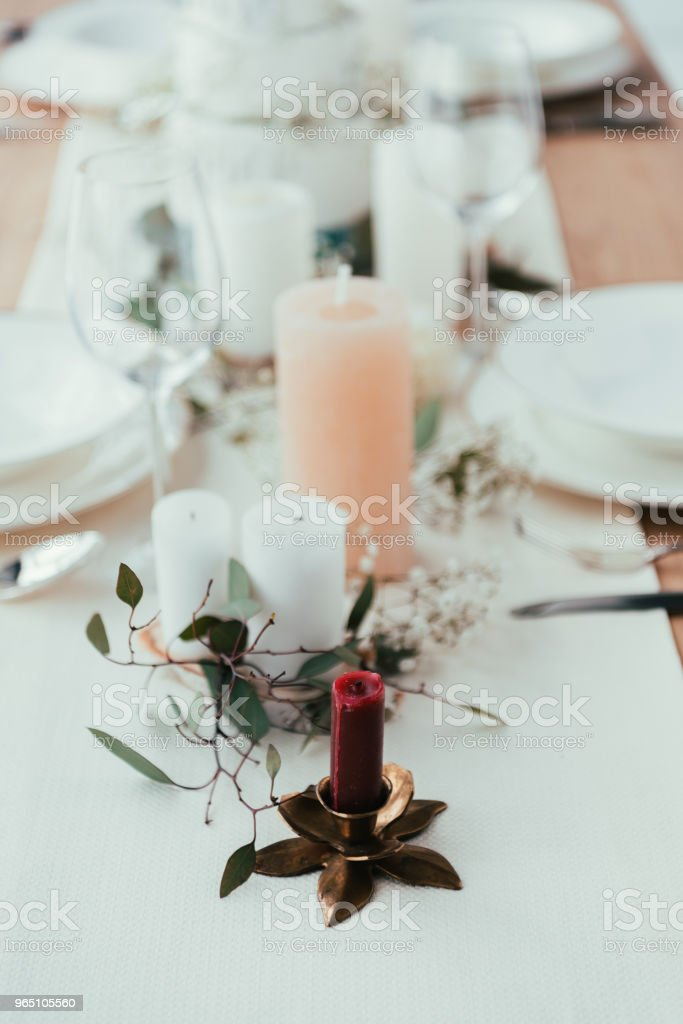 close up view of stylish table setting with candles, wineglasses and eucalyptus for rustic wedding royalty-free stock photo