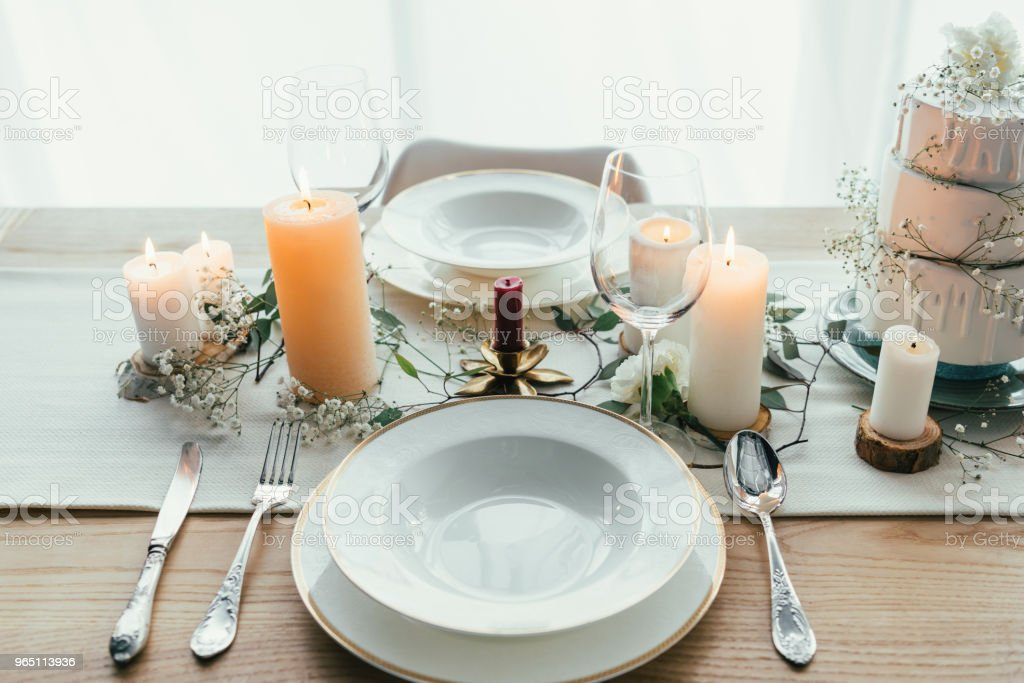 close up view of stylish table setting with candles, wineglasses and wedding cake for rustic wedding royalty-free stock photo