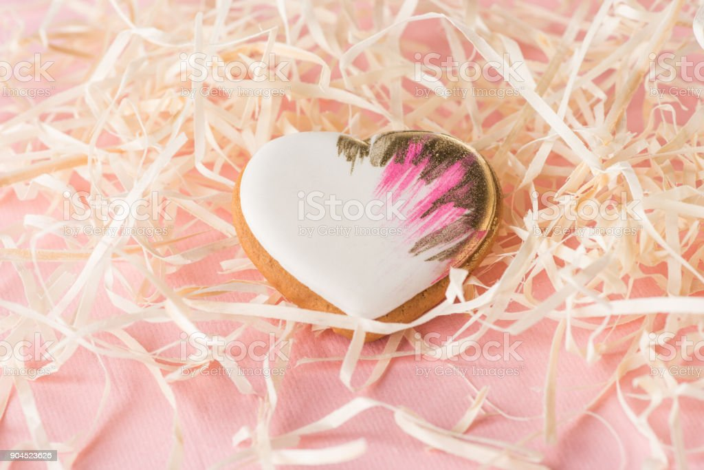 close up view of sweet heart shaped cookie and decorative straw on pink, st valentines holiday concept stock photo