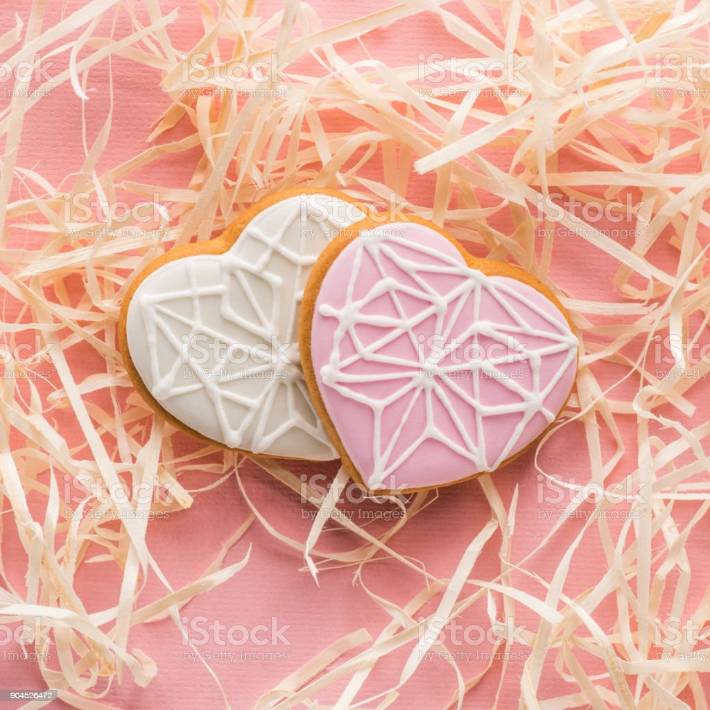 close up view of sweet heart shaped cookies and decorative straw on pink, st valentines holiday concept stock photo