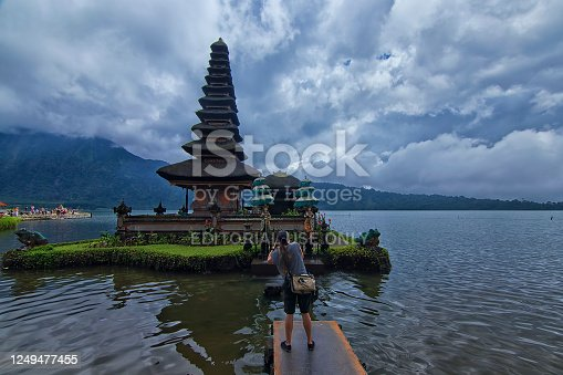 Female photographer composing her shot at the beautiful architectural design of the floating temple at Bratan Lake.