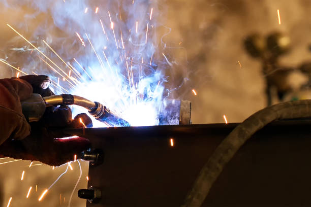 Close up view of the gas metal arc welding (GMAW), also known as metal inert gas or MIG welding. In addition to melting the base metal, a filler material is typically added to the joint to form a pool of molten material. Close up view of the gas metal arc welding (GMAW), also known as metal inert gas or MIG welding. In addition to melting the base metal, a filler material is typically added to the joint to form a pool of molten material. known gas stock pictures, royalty-free photos & images