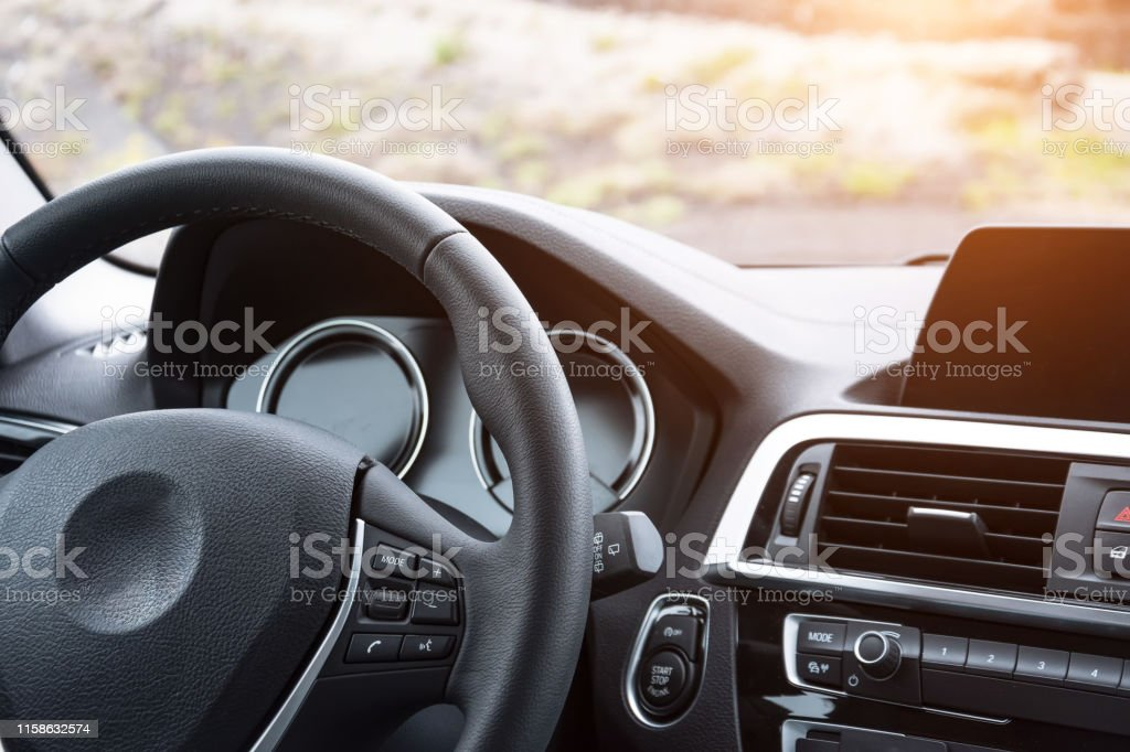 Close up view of the steering wheel and the front panel of the car, inside the cabin. Close up view of the steering wheel and the front panel of the car, inside the cabin Airbag Stock Photo