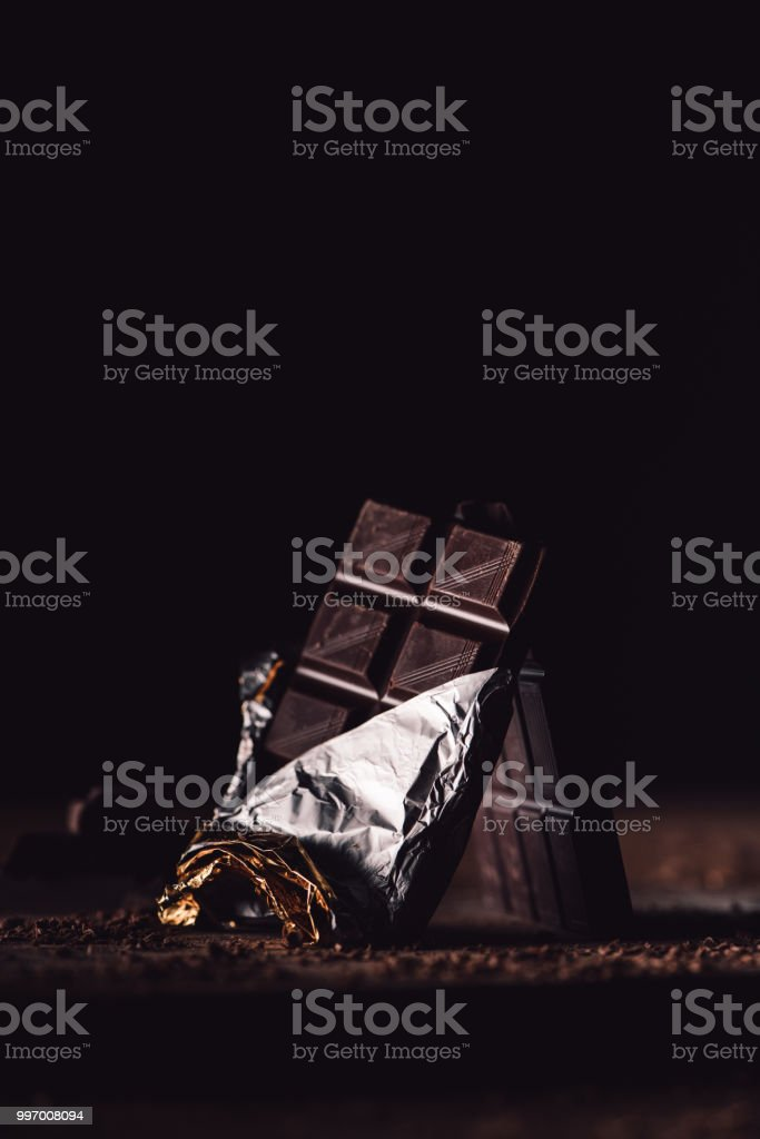 close up view of two arranged chocolate bars on wooden table on black...