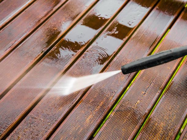 close up view of using pressure washer to clean impregnated wood terrace outdoors in the spring. - idropulizia ad alta pressione foto e immagini stock