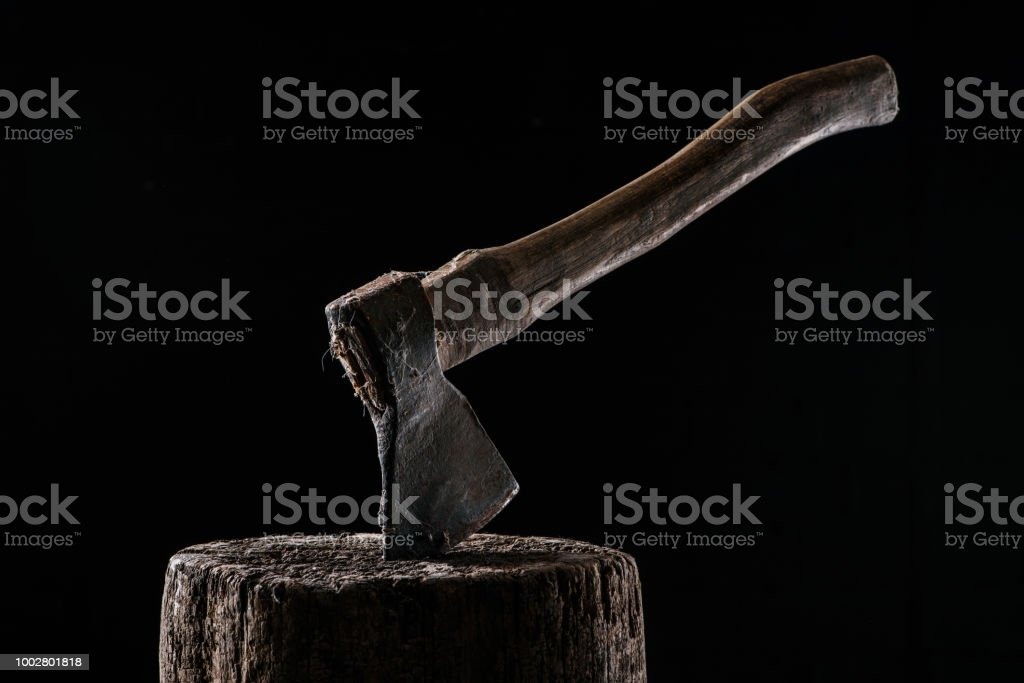 close up view of vintage axe on wooden stump isolated on black stock photo