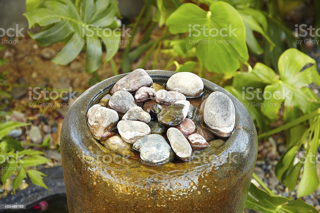 Close up view of water fountain filled with stones stock photo