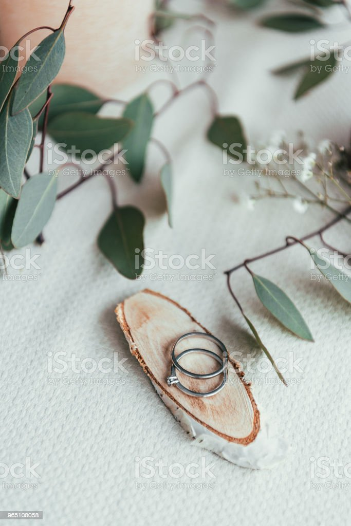 close up view of wedding rings on wooden decorative board and eucalyptus on tabletop royalty-free stock photo