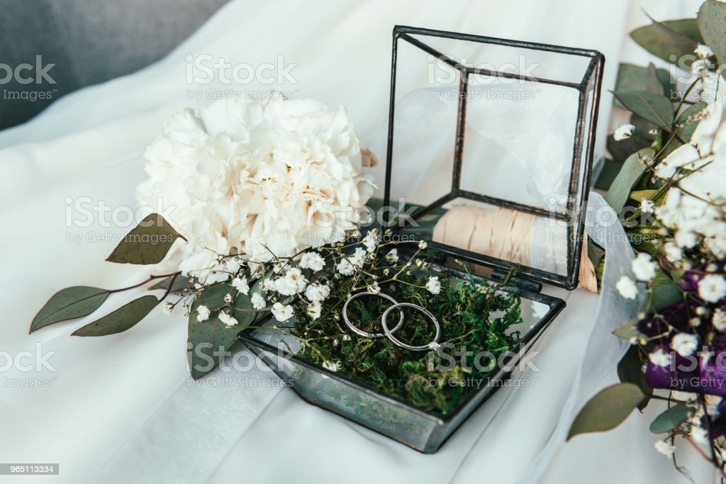close up view of white flowers, wedding rings in rustic box with plants inside zbiór zdjęć royalty-free