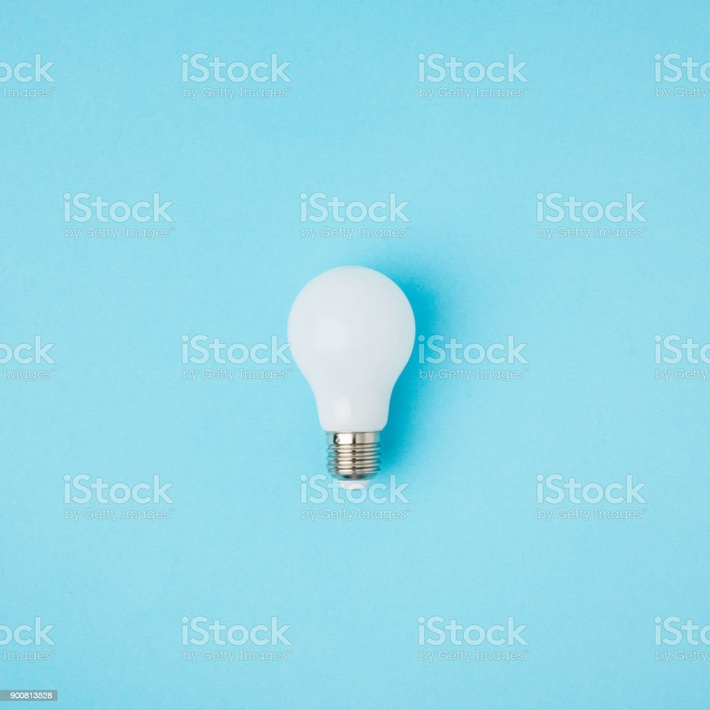 close up view of white light bulb isolated on blue stock photo